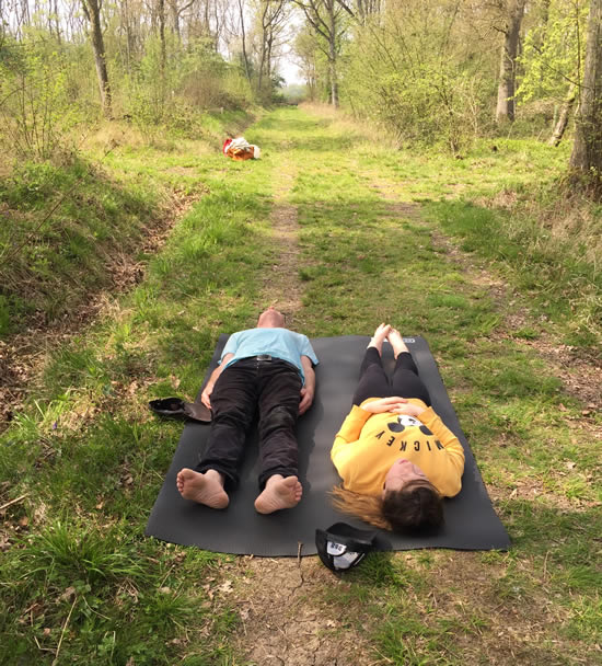 two people lying on a woodland track